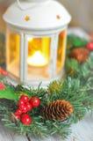 新年从一根冷杉木的` s花圈在白色木背景和一个蜡烛在一个白色烛台 免版税库存照片
