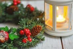 新年从一根冷杉木的` s花圈在白色木背景和一个蜡烛在一个白色烛台 免版税库存图片