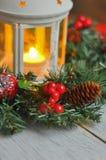 新年从一根冷杉木的` s花圈在白色木背景和一个蜡烛在一个白色烛台 图库摄影