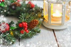 新年从一根冷杉木的` s花圈在白色木背景和一个蜡烛在一个白色烛台 库存图片