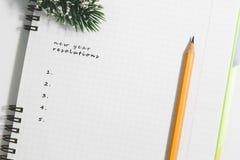 新年决议、笔记本和黄色铅笔有针叶树增殖比的 库存图片