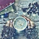 新年圣诞节 一杯咖啡或一杯茶在他的手和妇女上击碎了黑暗的巧克力,堆书 落的金锡 库存照片