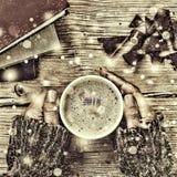 新年圣诞节 一杯咖啡或一杯茶在他的手和妇女上击碎了黑暗的巧克力,堆书 落的金锡 库存图片