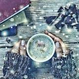 新年圣诞节 一杯咖啡或一杯茶在他的手和妇女上击碎了黑暗的巧克力,堆书 落的金锡 免版税库存照片