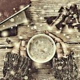 新年圣诞节 一杯咖啡或一杯茶在他的手和妇女上击碎了黑暗的巧克力,堆书 落的金锡 免版税库存图片