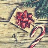 新年在一个自创箱子的` s礼物有在毛茸的云杉的分支和圣诞节棒棒糖附近的一把红色弓的 库存图片