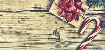 新年在一个自创箱子的` s礼物有在毛茸的云杉的分支和圣诞节棒棒糖附近的一把红色弓的 图库摄影