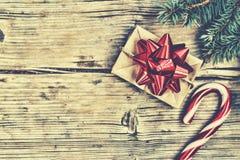 新年在一个自创箱子的` s礼物有在毛茸的云杉的分支和圣诞节棒棒糖附近的一把红色弓的 库存照片
