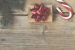 新年在一个自创箱子的` s礼物有在毛茸的云杉的分支和圣诞节棒棒糖附近的一把红色弓的 免版税库存照片