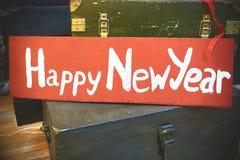 新年在一块木减速火箭的牌的` s标志 库存图片