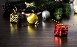 新年在红色包装的` s礼物与在圣诞树特写镜头宏指令的爪子的附近一把金弓在一张木桌上的 免版税库存图片