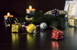 新年在红色包装的` s礼物与在圣诞树特写镜头宏指令的爪子的附近一把金弓在一张木桌上的 库存照片