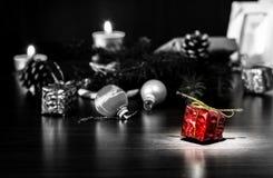 新年在红色包装的` s礼物与在圣诞树特写镜头宏指令的爪子的附近一把金弓在一张木桌上的 免版税库存照片