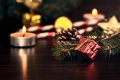 新年在红色包装的` s礼物与在圣诞树特写镜头宏指令的爪子的附近一把金弓在一张木桌上的 图库摄影