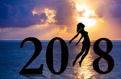 新年好卡片2018年 少妇剪影跳跃作为第2018标志的部分的海滩的有日落背景 免版税图库摄影
