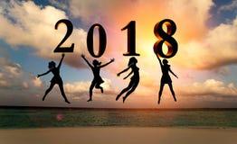新年好卡片2018年 现出轮廓跳跃在海的热带海滩和2018数字的妇女有日落背景 库存照片