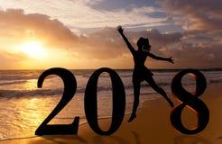 新年好卡片2018年 现出轮廓跳跃在海的热带海滩和2018数字的少妇有日落背景 免版税库存图片
