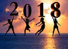 新年好卡片2018年 现出轮廓跳跃在海的热带海滩和2018数字的少妇有日落背景 图库摄影