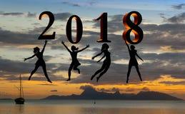 新年好卡片2018年 现出轮廓跳跃在海的热带海滩和2018数字的少妇有日落背景 库存图片