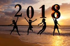 新年好卡片2018年 现出轮廓跳跃在海的热带海滩和2018数字的少妇有日落背景 免版税库存照片