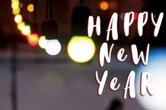新年好在减速火箭的诗歌选电灯泡的文本标志在街道 免版税图库摄影