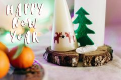 新年好在圣诞节土气桌上的文本标志与蜡烛w 免版税库存照片