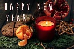 新年好在圣诞节蜡烛和石榴石曲奇饼的文本标志 库存照片