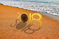 新年好在2018年与在海滩背景的老时钟 免版税库存图片