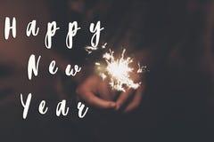 新年好文本标志,拿着灼烧的闪烁发光物烟花孟加拉光的手 空间为 免版税库存照片