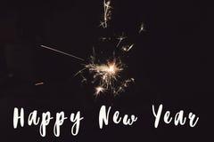 新年好文本标志,拿着灼烧的闪烁发光物烟花孟加拉光的手 空间为 库存照片