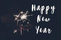 新年好文本标志,拿着灼烧的闪烁发光物烟花孟加拉光的手 空间为 库存图片