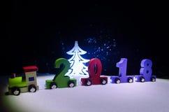 2018新年好,木玩具火车运载的数字在雪的2018年 玩具火车与2018年 复制空间 圣诞节装饰装饰新家庭想法 免版税库存照片