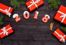 新年好2018从红色和白色姜饼曲奇饼的标志标志在与红色礼物盒的黑暗的木背景,拷贝空间 免版税库存图片