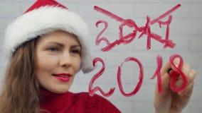 新年好 圣诞老人女孩在玻璃词新年好写唇膏 传送信息的帽子的美丽的女孩 图库摄影