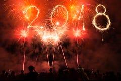 新年好2018年写与闪烁发光物和五颜六色的烟花作为背景 庆祝党人 免版税图库摄影