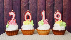 新年好2019年,在杯形蛋糕的数字蜡烛有木背景 影视素材