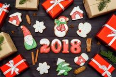 新年好2018标志标志、红色和白色姜饼曲奇饼和礼物盒在黑暗的木背景 顶视图,平的位置 库存图片