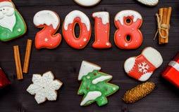 新年好2018标志标志用在黑暗的木背景,拷贝空间的红色和白色姜饼曲奇饼 顶视图,平的位置 图库摄影