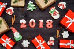 新年好2018标志标志用在黑暗的木背景,拷贝空间的红色和白色姜饼曲奇饼 顶视图,平的位置 免版税库存图片