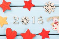 2018新年好 红色圣诞节的装饰,黄色星、天使、雪花和心脏在浅兰的木背景 12月2018 图库摄影