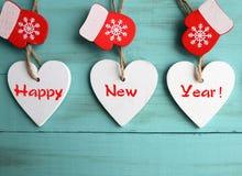 新年好 装饰白色木圣诞节心脏和红色手套在蓝色木背景 寒假概念 免版税库存图片