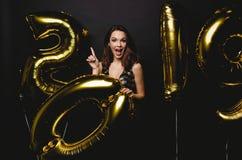新年度 有气球的妇女庆祝在党的 美丽的微笑的女孩画象发光的礼服投掷的五彩纸屑的 免版税图库摄影