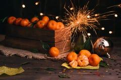 新年度`s概念 在一个木箱的蜜桔 闪烁发光物在花瓶烧 图库摄影