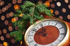 新年快乐自午夜2018年,有假日光的老木时钟和冷杉分支 库存图片