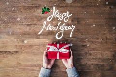 新年快乐问候文本和礼物在木背景 图库摄影
