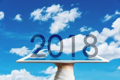 新年快乐2018年,拿着有被增添的现实蓝天和白色云彩的手数字式片剂 免版税库存图片