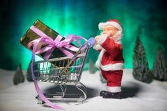 新年或圣诞节假日购物概念 存放促进 运载在雪的圣诞老人项目台车推车 免版税库存照片