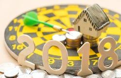 新年概念、2018数字在硬币与房子模型和硬币 图库摄影