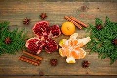 新年概念圣诞节  新鲜的可口石榴石、柑橘、桂香和茴香在木桌上 平的位置 顶视图 免版税图库摄影