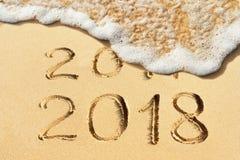 新年概念- 2017年和2018手写在沙滩 免版税图库摄影